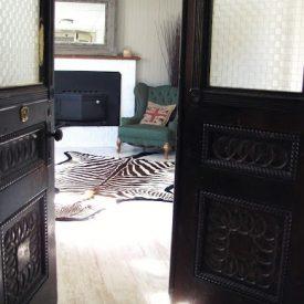 Svarte dører åpne med utsikt til stue med sebraskinn foran grønn lenestol.