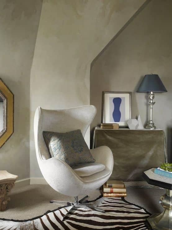 Stol i råstilig design i rom med teppe og sebrafell.